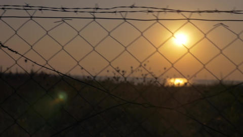 Beautiful sunset seen through barbed wire Footage