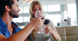Happy young couple toasting glasses of wine while having meal Footage