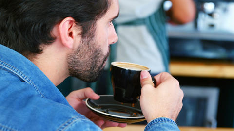 Focus of man is drinking coffee at counter Live Action