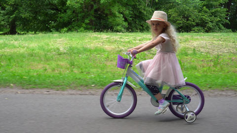 smiling cute girl cycling in the park. Gimbal parallel movement shot GIF
