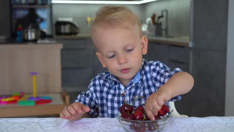 Baby boy eating cherries sitting in kitchen. Cherries in plate on table. Gimbal GIF