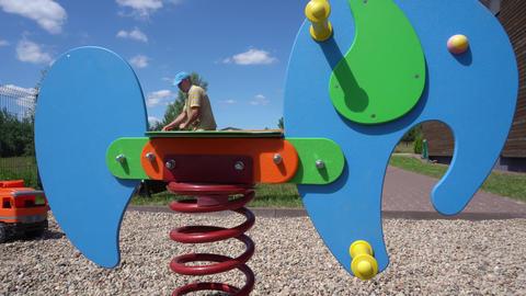 Man mowing lawn near children playground in the yard. Gimbal shot GIF