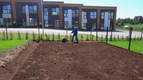 Professional worker man pulls lawn roller for flatten yard soil. Gimbal motion GIF