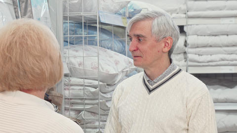 Senior man choosing bedding goods with his wife at furnishings store Live Action