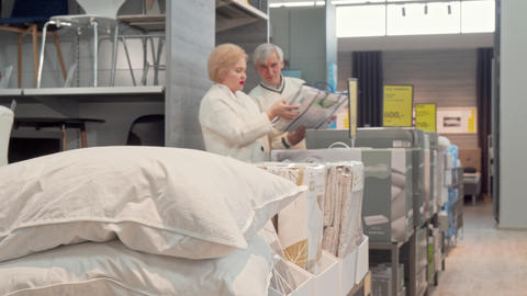 Senior couple shopping for new comfortable sleep pillows at furnishings store Footage