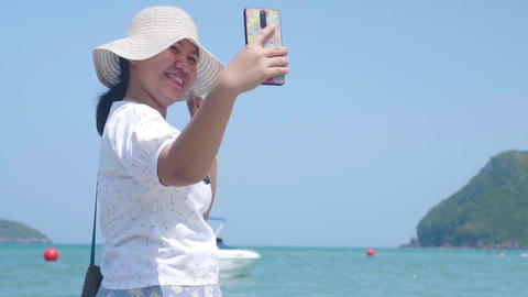 Asian lady selfie herself at the beach with crystal blue sea at background. Paradise Islands. Slow Footage