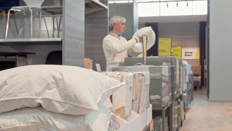 Senior man shopping for orthopedic pillow at furnishings store Live Action