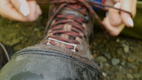 Big mountain boot with multicolored laces standing on mountain soil Live Action