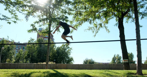 Young Man Training As Acrobat With Trickline In City Park Footage