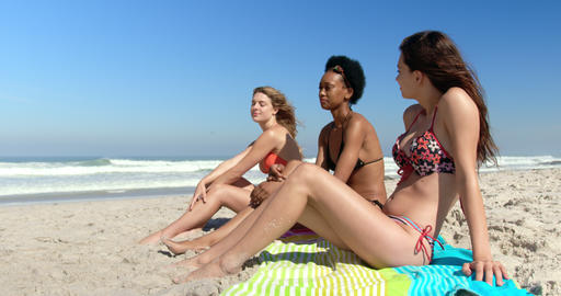 Young female friends sitting together at beach 4k Stock Video Footage