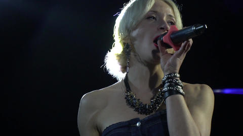 Close up of a blonde woman with a microphone singing on stage Live Action