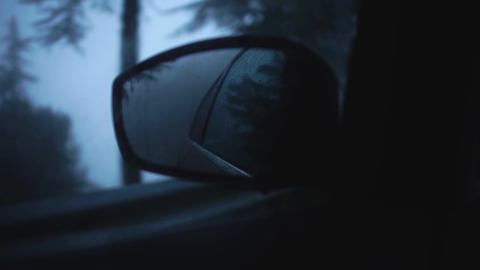 Reflection of rainy evening street in the side mirror of a moving car driving in Footage