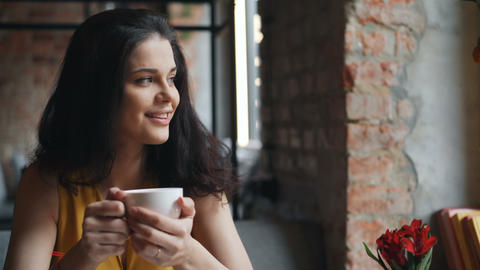 Cheerful girl drinking tea in cafe holding cup and smiling enjoying drink Footage
