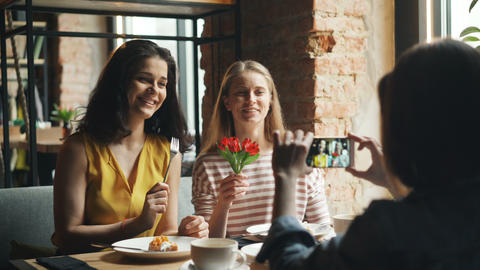 Carefree women posing for smartphone camera in cafe holding flower having fun Footage