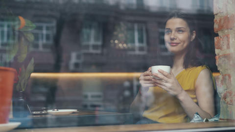 Happy young lady drinking coffee looking out of window sitting in cafe alone Live Action