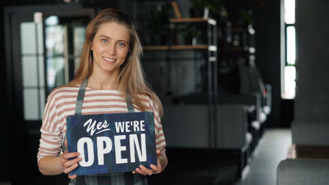 Portrait of attractive blond waitress holding open sign in new cafe smiling Footage