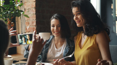 Pretty ladies drinking coffee in cafe and taking photos with smartphone laughing Footage