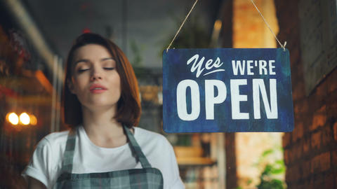 Beautiful waitress closing coffee shop in evening hanging closed sign on door Live Action