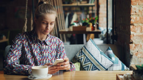 Attractive young woman using modern smartphone in coffee shop touching screen Footage