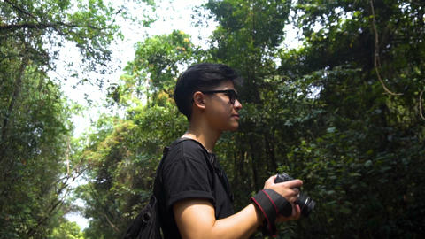 Good looking asian guy standing to refresh himself with forest. feel amazing. take a picture of it Footage