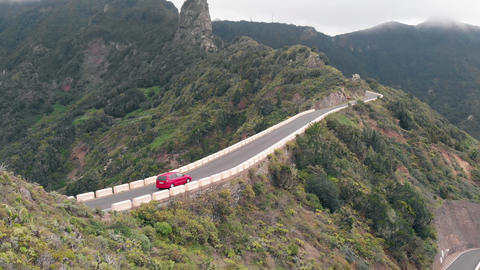 Aero view - a lonely car drives through a narrow and dangerous road high in the Live Action