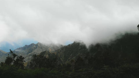 Aerial. Beautiful thick and dense clouds fly low over a green valley in a Footage