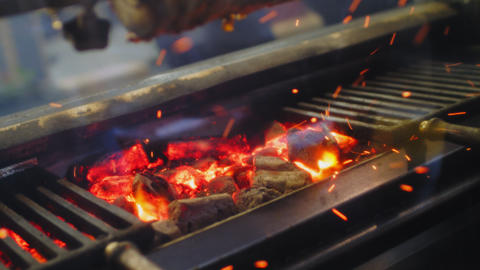 red hot embers and sparks under grill metal grid close view Footage
