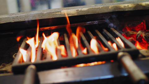 stove and burning fire under metal grids in street food cafe Footage