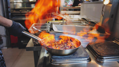 man adds oil to meat and burns fire preparing food in cafe Footage