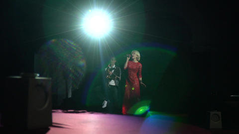 Two people are performing on stage with a single big light behind them Live Action