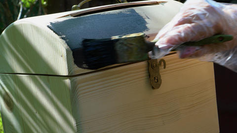 Man puts black paint brush on the lid of a wooden chest Stock Video Footage