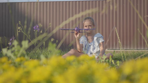 Cute girl with a toy plane sitting on the green grass in the yard. Girl having Footage