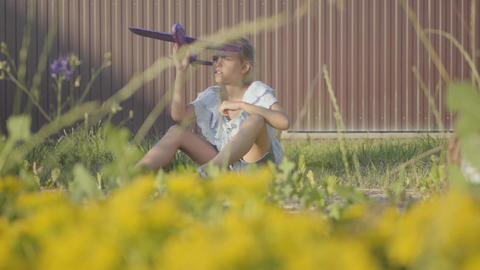 Portrait of a pretty cute little girl playing with the small plane sitting on Footage