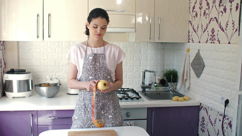 Woman peels an apple at kitchen Footage