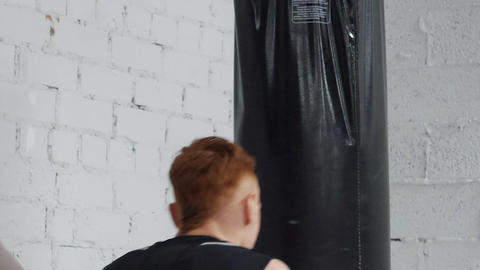 Aggressive boxer on intensive training. He practices punching with punching bag Footage