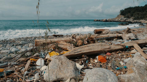 Trash, plastic, garbage, environmental pollution on the seashore. Waves in slow Footage