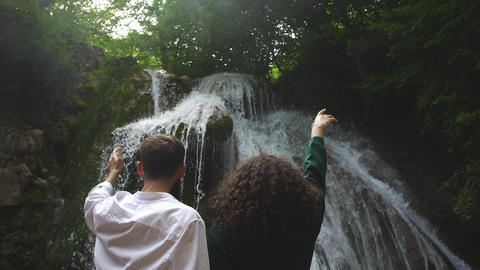 Man and woman straight his hands to forest waterfall Freshness feel in the air Footage