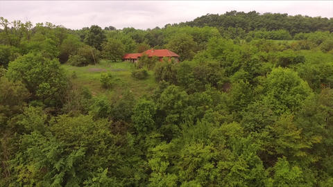 Flying near the house which is located in the forest Footage
