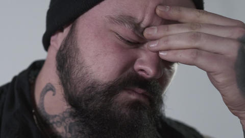 Aggressive bearded man rubbing his forehead to hold back emotions. The brutal Footage