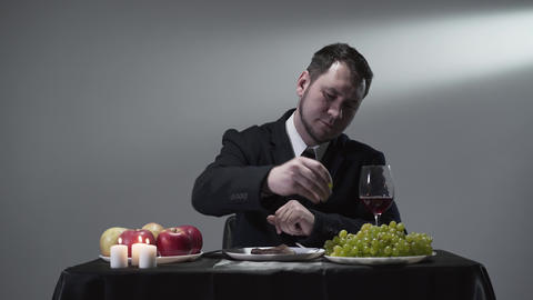 Rich businessman in a suit eatting or tasting a piece of meat next to apples Live Action