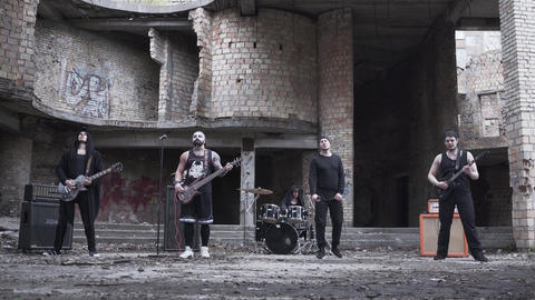 Rock band playing music in the abandoned building. Brutal men starred in a music Footage