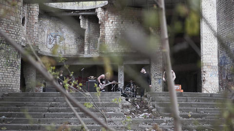 Rock band playing music in the abandoned building. Brutal men starred in a music Live Action