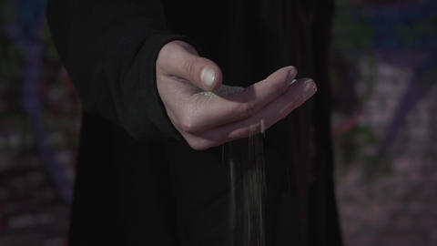 Male hand with the sand close-up. The sand flows through the fingers of a man Footage