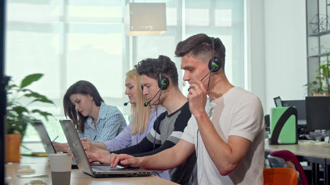 Friendly young man smiling to the camera, working at customer support call Live Action