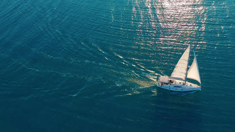Aerial view. Yacht sailing on open sea at sunny day. Sailing boat in sea Footage
