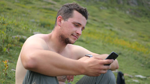 Happy man sitting and looking at his phone in the Georgian Mountains in slo-mo Live Action