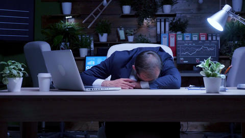 Overworked businessman fell asleep at night in the office Live Action