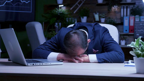 Male business person is asleep in the office at night Live Action