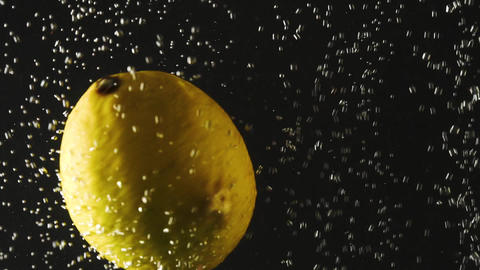 Fresh lemon falling into the water with bubbles on black background. Fresh Live Action