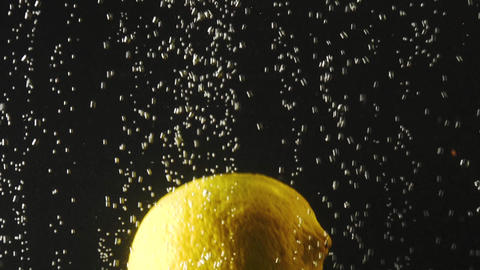 Fresh lemon falling into the water with bubbles on black background. Fresh Footage
